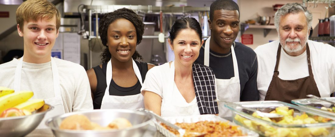 Diverse group of volunteers in kitchen smiling with meal they all helped to prepare